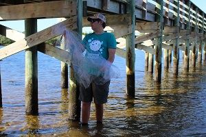 Young man in Coastal Cleanup t-shirt, standing in ankle-deep water, holding debris.