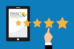 Image of tablet with Pasco County Logo, 5 stars and a hand with finger pointing to stars.