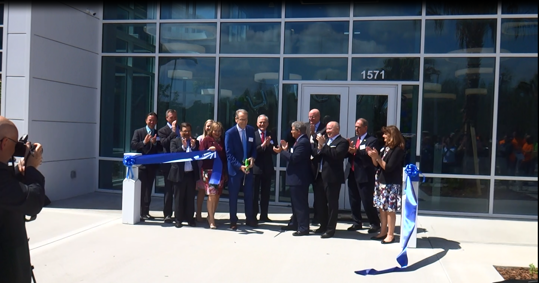 Group of people cutting a blue ribbon in front of Mettler Toledo